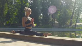 Young woman doing yoga exercises in the park stock footage