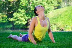 Young woman doing yoga exercises in park - cobra pose Royalty Free Stock Photos