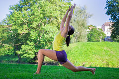 Young woman doing yoga exercises in park - crescent moon pose Royalty Free Stock Photography