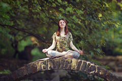 Young woman doing yoga exercises in park's bridge. Royalty Free Stock Photography