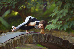 Young woman doing yoga exercises in park's bridge. Royalty Free Stock Photos