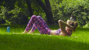 Young woman doing yoga exercises in the park. Warming-up stock video footage