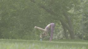 Young woman doing yoga exercises in the park. Warming-up. Log stock footage