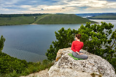 Young woman is doing yoga exercises on the rock above beautiful river. Stock Photography