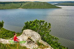 Young woman is doing yoga exercises on the rock above beautiful river. Royalty Free Stock Images