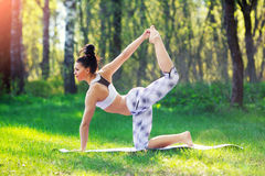 Young woman doing yoga exercises in the summer city park. Health lifestyle concept. stock photography