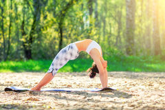 Young woman doing yoga exercises in the summer city park. Health lifestyle concept. stock photo
