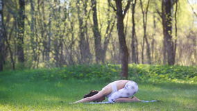 Young woman doing yoga exercises in the summer city park. Health lifestyle concept. stock footage