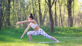 Young woman doing yoga exercises in the summer city park. Health lifestyle concept. stock video