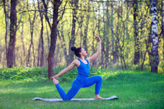 Young woman doing yoga exercises in the summer city park. Health lifestyle concept. stock images