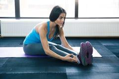 Young woman doing yoga exercises on yoga mat. Young fit woman doing yoga exercises on yoga mat at gym Stock Photo