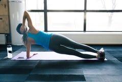 Young woman doing yoga exercises on yoga mat. Young fit woman doing yoga exercises on yoga mat at gym Stock Image
