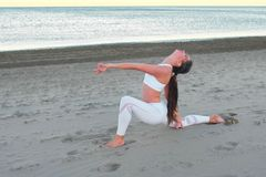 Young woman is doing yoga High Lunch Pose on the sand beach at sunrise in autumn. stock photography