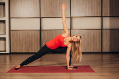 Young woman doing yoga at home gym stock photo