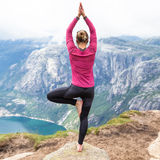 Young woman doing yoga on Kerag. Happy  enjoy beautiful lake and good weather in Norway. Royalty Free Stock Photo