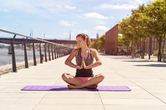 Young woman doing yoga lotus position in the city by the river, Stock Photography