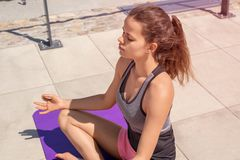 Young woman doing yoga lotus position in the city by the river,. In sport clothes, relaxed and calm positive meditation Royalty Free Stock Photos