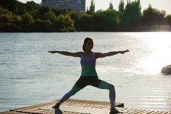 Young woman doing yoga in morning park near lake. stock photos