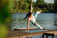 Young woman doing yoga in morning park. stock photos