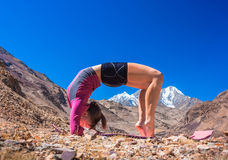 Young woman doing yoga in mountain landscape Stock Images