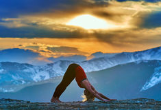 Young woman doing yoga in the mountains Stock Images