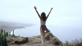 Young woman doing yoga in the mountains standing on one leg overlooking the ocean