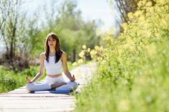 Young beautiful woman doing yoga in nature. Young woman doing yoga in nature. Female wearing white sport clothes in lotus figure Stock Photo