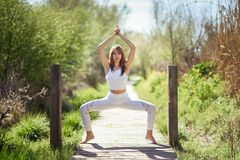 Young beautiful woman doing yoga in nature. Young woman doing yoga in nature. Female wearing white sport clothes on a wooden road Royalty Free Stock Photo