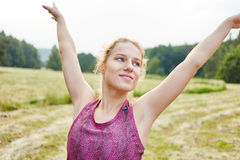 Young woman doing yoga in the nature. Stretching her arms Royalty Free Stock Photos