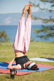 Young woman is doing yoga near lake Royalty Free Stock Image