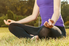 Young woman doing yoga outdoor. Young woman sitting in lotus pose outdoors Royalty Free Stock Photo