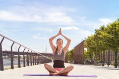 Young woman doing yoga outdoors in the city with hands up, lotus. Position Royalty Free Stock Image
