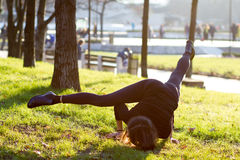 Young woman doing yoga in park. Young woman in arm stand yoga position in park on sunny day royalty free stock image