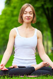 Young woman doing yoga in the park. Stock Photos