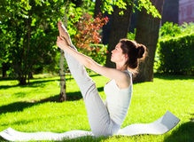Young woman doing yoga in the park in the morning Stock Image