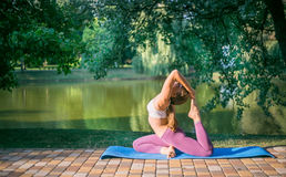 Young woman doing yoga in Park near lake Royalty Free Stock Images