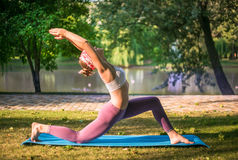 Young woman doing yoga in Park near lake Royalty Free Stock Photography