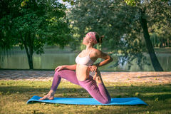 Young woman doing yoga in Park near lake Stock Image