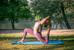 Young woman doing yoga in Park near lake Stock Images