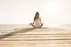 Young Woman Doing Yoga On Pier Stock Photos