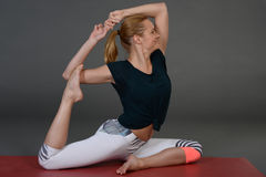 Young woman doing yoga or pilates exercise on mat. Royalty Free Stock Photos