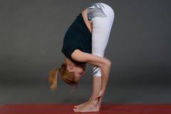 Young woman doing yoga or pilates exercise on mat. Stock Photography