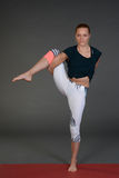 Young woman doing yoga or pilates exercise on mat. Royalty Free Stock Image