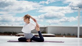 Young woman doing yoga or pilates exercise one legged king pigeon pose. Eka pada rajakapotasanain in slow motion. Flexible girl is doing stretching in stock footage