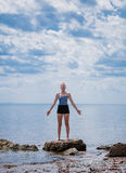 Young Woman doing Yoga Position. In Front of the Ocean royalty free stock photography