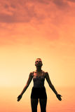 Young Woman doing Yoga Position in Front of the Ocean. During Sunset royalty free stock photos