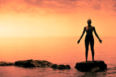 Young Woman doing Yoga Position in Front of the Ocean. During Sunset stock photo