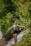 Young Woman doing Yoga Position Near a Waterfall Stock Photography