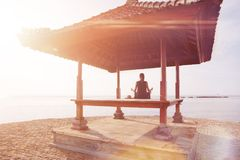 Young woman doing yoga practice on the beach Royalty Free Stock Photography