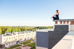 Young woman doing yoga on the roof stock photos